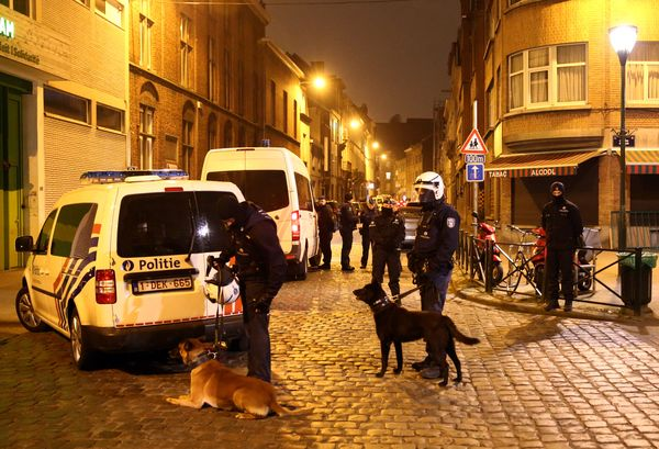 Police officers guard a road after the raid in which Salah Abdeslam was arrested.