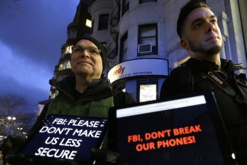 FILE - In this Tuesday, Feb. 23, 2016, file photo, demonstrators Peter Brockmann, of Northborough, Mass., left, and Chris Gladney, of Boston, right, display iPads with messages on their screens outside an Apple store in Boston. The FBI's victory in breaking into a San Bernardino killer's iPhone without Apple's help merely prolonged a battle over how far the government can go to examine private messages, photos and other files. (AP Photo/Steven Senne, File)