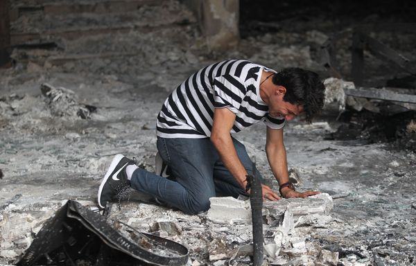 A man in a building destroyed by the ISIS bombing in Baghdad.