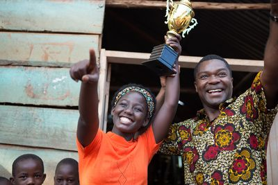 "Madina Nalwanga and David Oyelowo holding a trophy in ""Queen of Katwe"""