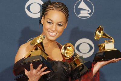Alicia Keys holds her 2002 Grammys, one of which was for Best Female R&B Vocal Performance, an award that no longer exists.